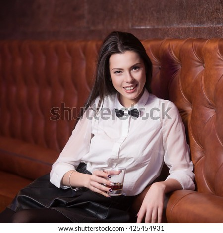 Beautiful smiling brunette girl in white shirt and black bow tie at nightclub celebrating, holding glass with drink at party - stock photo