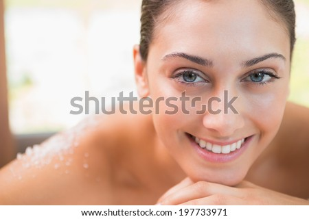Beautiful smiling brunette lying on massage table with salt scrub on back in the health spa - stock photo