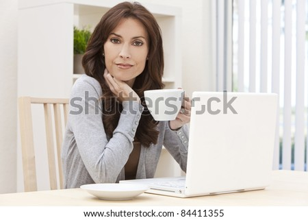 Beautiful, smiling, brunette woman at home at a table using her laptop computer drinking a mug of tea or coffee