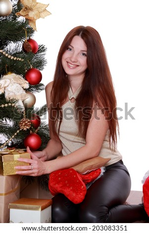 beautiful smiling brunette womansitting over Christmas tree on Holiday theme - stock photo