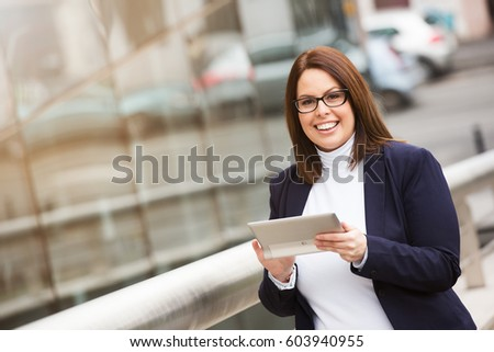 Beautiful smiling business woman outside portrait. Working on a digital tablet.