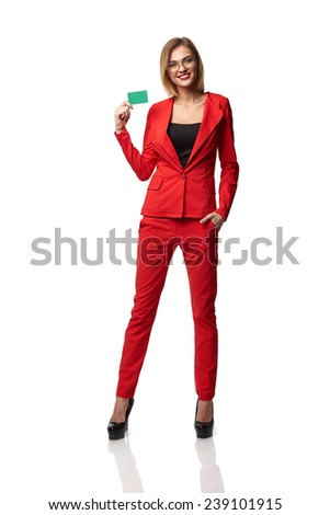 Beautiful smiling business woman wearing spectacles and in the red, holding a card in hand, isolated on white background - stock photo