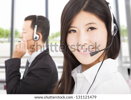 beautiful smiling businessman with call center agent - stock photo