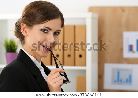 Beautiful smiling businesswoman put glasses in mouth standing in office portrait. Successful woman in suit looking in camera. Serious business, exchange market, job offer, excellent education concept - stock photo