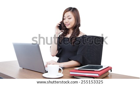 Beautiful smiling businesswoman talking on a cellphone. Sitting talking mobile phone at her desk. Mixed race chinese / caucasian model isolated on seamless white background. - stock photo