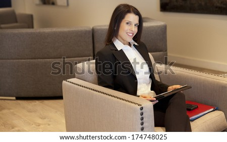 Beautiful Smiling Businesswoman working on tablet at the hotel - stock photo