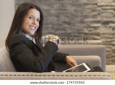 Beautiful Smiling Businesswoman working on tablet at the office - stock photo