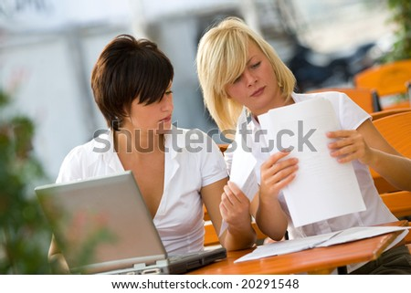 Beautiful smiling businesswomen in cafe with laptop and papers