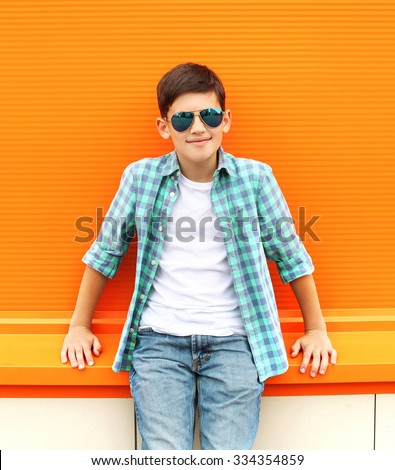 Beautiful smiling child boy wearing a sunglasses and shirt in city - stock photo
