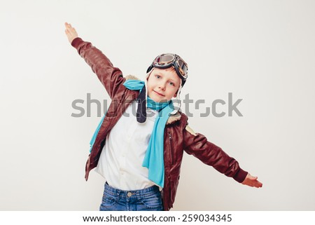 Beautiful smiling child (kid, boy) in helmet on a grey background. Vintage pilot (aviator) concept. - stock photo