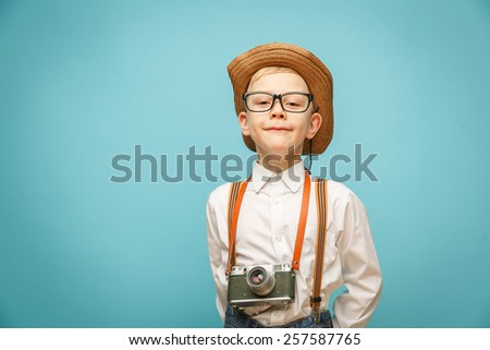 Beautiful smiling child (kid, boy) - photographer holding a instant camera - stock photo