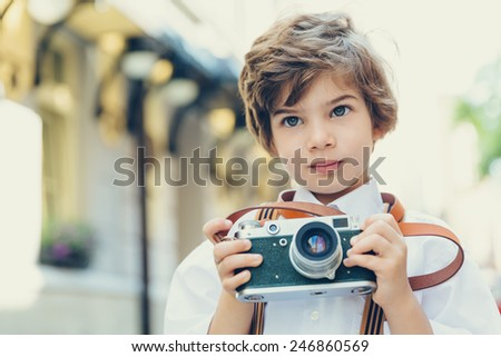 Beautiful smiling child (kid, boy) - photographer  holding a instant camera outdoors - stock photo
