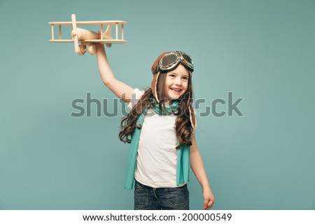 Beautiful smiling child (kid, girl) in helmet on a blue background playing with a plane. Vintage pilot (aviator) concept - stock photo