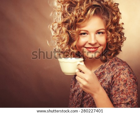 Beautiful smiling curly woman drinking a cup of coffee - stock photo