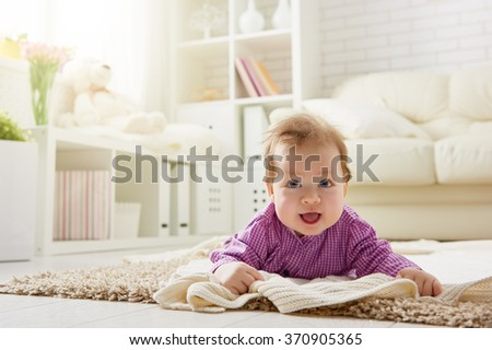 Beautiful smiling cute baby girl in the room. Happy child laughing. - stock photo