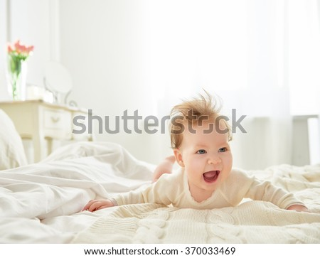 Beautiful smiling cute baby girl on the bed in the room. Happy child laughing. - stock photo