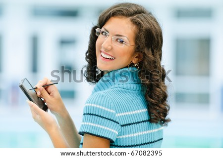 Beautiful smiling dark-haired woman in dark blue sweater and glasses writes with help stylus on pocket computer against spacious light hall. - stock photo