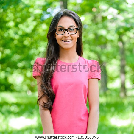 Beautiful smiling dark-haired young woman in pink dress, against background of summer green park.