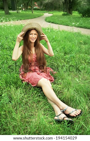 beautiful smiling dreaming woman in a hat in a summer park on a background of green grass