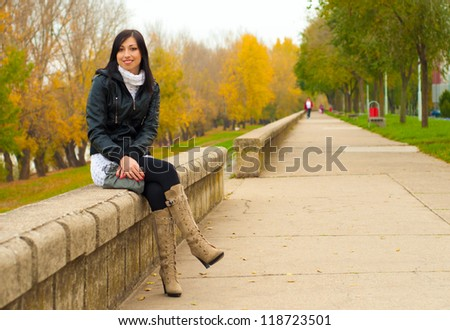Beautiful smiling elegant girl sitting outdoors on cloudy autumn day.