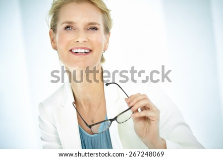 Beautiful smiling elegant woman indoors wearing business attire, white blazer and short blond hair. Professional woman holding glasses. - stock photo