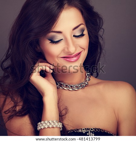 Beautiful smiling evening makeup woman with long curly hairstyle looking down in pearl bangle and fashion necklace. Toned closeup portrait