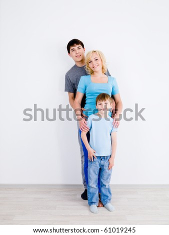 Beautiful smiling family with son standing in line together in empty room