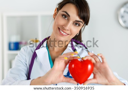 Beautiful smiling female doctor holding red heart in front of chest closeup. Medical help, prophylaxis, insurance, surgery and resuscitation concept. Cardiology care,health, protection and prevention - stock photo