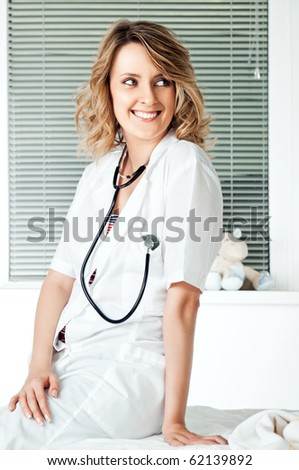 Beautiful smiling female doctor with stethoscope leaning on a couch - stock photo