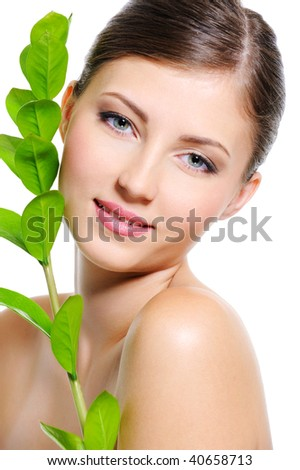 Beautiful smiling female face with a clean healthy skin and plant near her body - stock photo