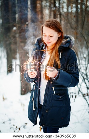 Beautiful Smiling Female in Warm Clothing Holding Sparklers in Winter Forest. Festive Mood. - stock photo
