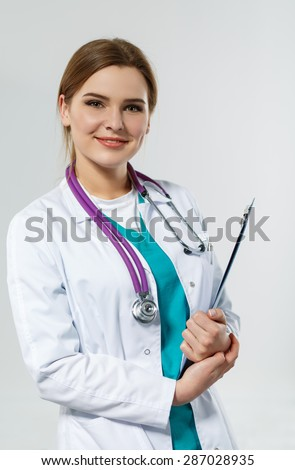 Beautiful smiling female medicine doctor holding clipped document pad. Medical help or insurance concept. Doctor is waiting for patient to examine. Physician reception concept - stock photo