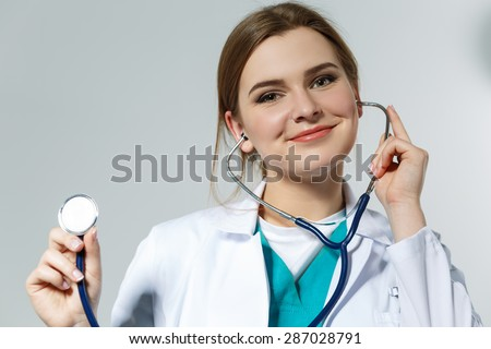 Beautiful smiling female medicine doctor holding stethoscope's head closeup. Medical help or insurance concept. Doctor is ready to examine patient and help. Medical concept. - stock photo