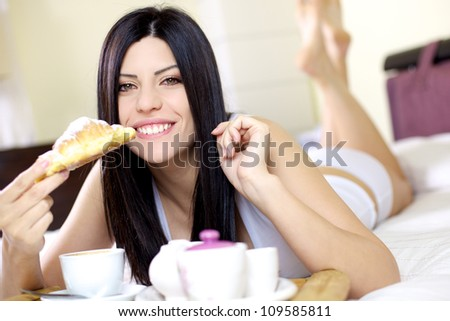beautiful smiling female model eating croissant in bed - stock photo