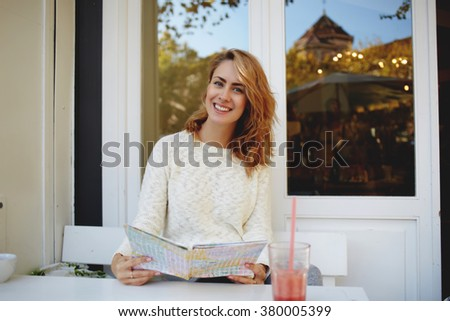 Beautiful smiling female traveler examines local map while sitting in modern sidewalk cafe during free time, cheerful woman tourist enjoying rest in cozy coffee shop during summer vacation overseas - stock photo
