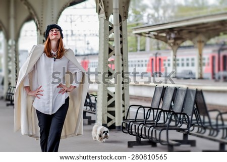 Beautiful smiling ginger hair woman in hat with veil and shih tzu doggy walking on the platform at the Vitebsk railway station in St.-Petersburg, Russia