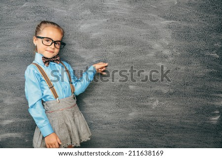 Beautiful smiling girl against chalkboard. School concept - stock photo