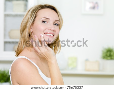 Beautiful smiling girl applying moisturizer cream on face standing in the bathroom - stock photo