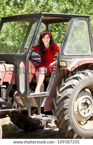 Beautiful smiling girl driving tractor