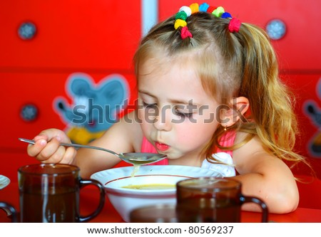 Beautiful smiling girl eating soup from a plate - stock photo