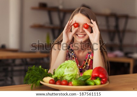beautiful smiling girl holding vegetables in their hands - stock photo
