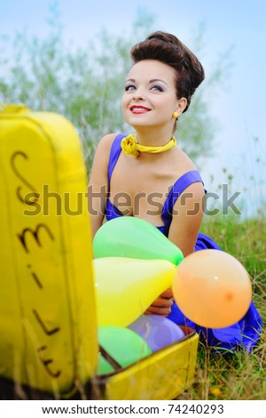 beautiful smiling girl in a blue dress with a yellow suitcase and colorful balloons