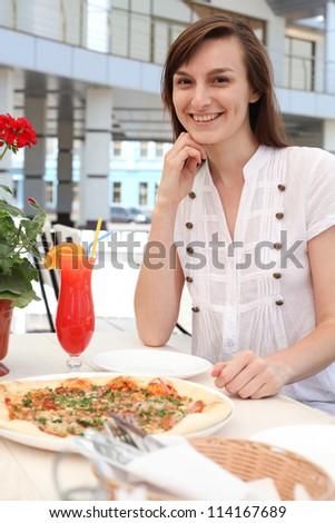 Beautiful smiling girl in a cafe - stock photo