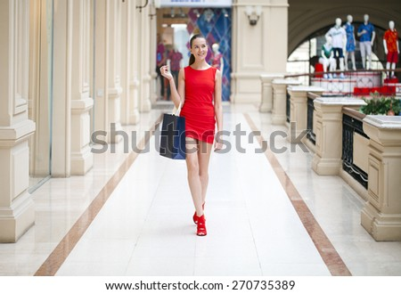 Beautiful smiling girl in a red dress, holding shopping bags walking in the shop - stock photo