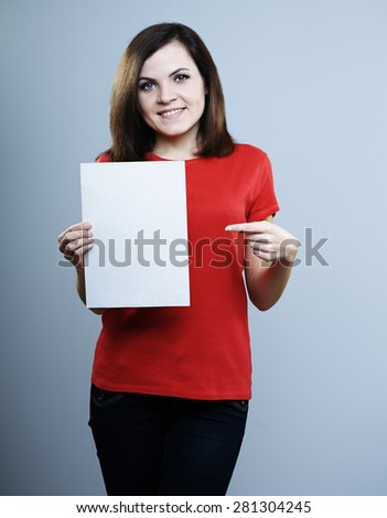 beautiful smiling girl in a red shirt holding a poster with the other hand shows a finger at him