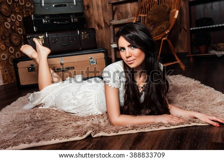 beautiful smiling girl in a white dress lying on a carpet in the interior studio with wooden walls