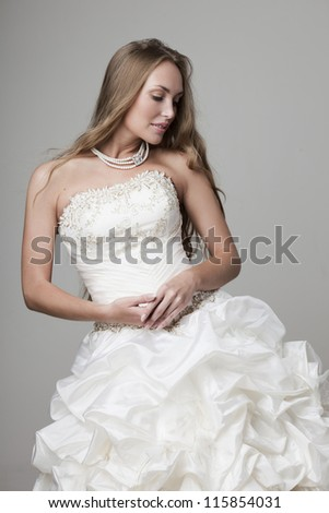 beautiful smiling girl in a white wedding dress on a gray background