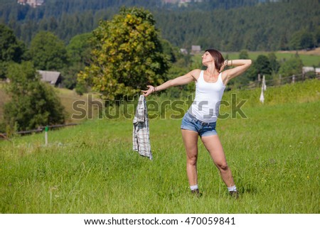 Beautiful smiling girl in country style dress posing at grass meadow