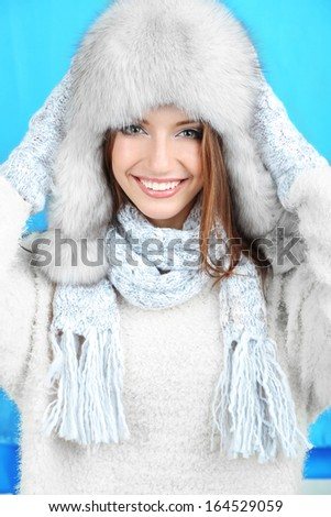Beautiful smiling girl in hat and mittens on blue background