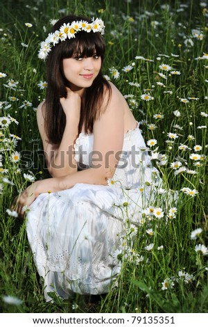 beautiful smiling girl in the chamomile field